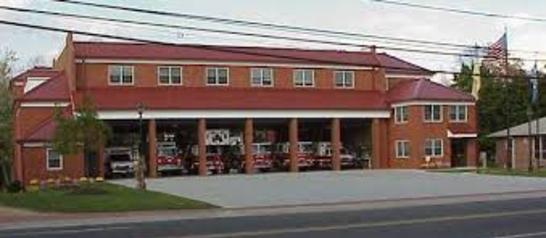 Picture of Station 221 from across the street with the bay doors opened viewing the apparatus